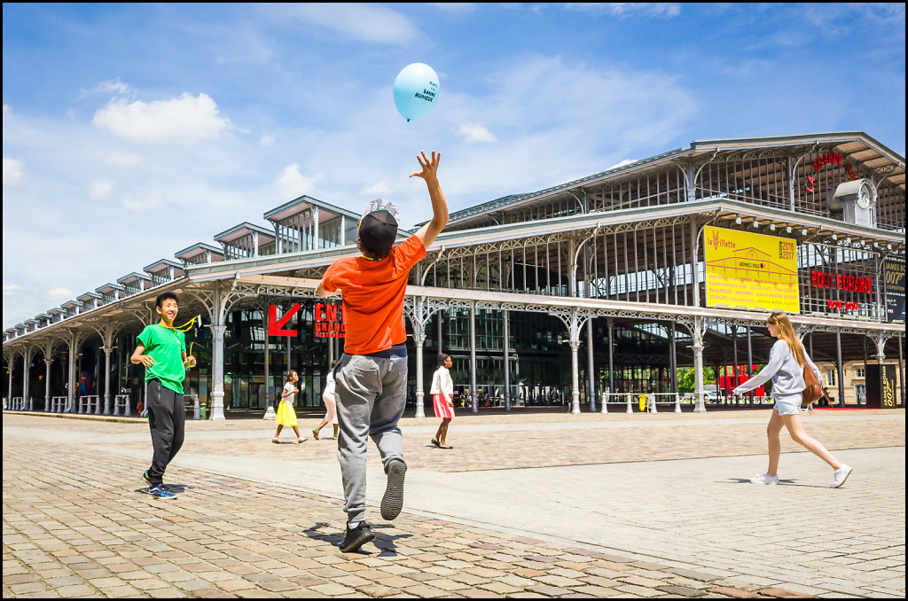 Teenagers playing with a balloon in front of the Grande Halle de